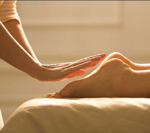 hands over feet on massage table